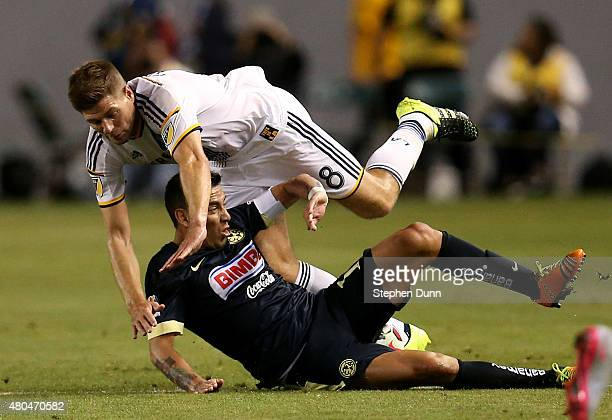 Steven Gerrard of the Los Angeles Galaxy tumbles over Rubens Sambueza of Club America in the International Champions Cup 2015 at StubHub Center on...