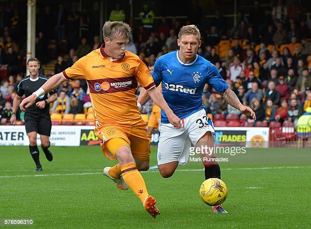 Steven Hammell of Motherwell clears the ball from Martyn Waghorn of Rangers during the Scottish League Cup First Round Group Stage match between...