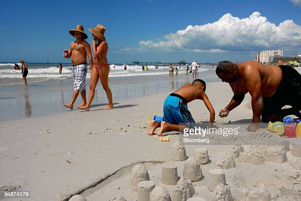Steven Hendricks far right and his son Aaron play in the white sand in Clearwater Beach Florida US on Saturday Sept 13 2008 As few as 50 miles out in...