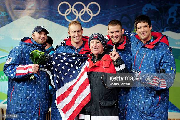 Steven Holcomb Curtis Tomasevicz a coach Justin Olsen and Steve Mesler of USA 1 celebrate after winning the gold medal during the men's four man...