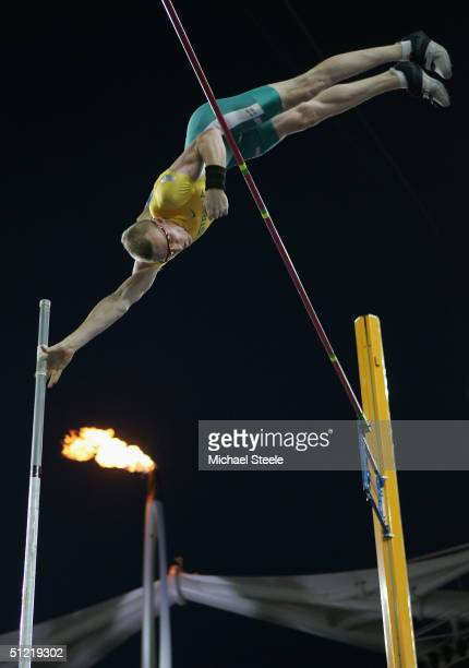 Steven Hooker of Australia jumps in front of the Olympic flame during the men's pole vault qualifying round on August 25 2004 during the Athens 2004...