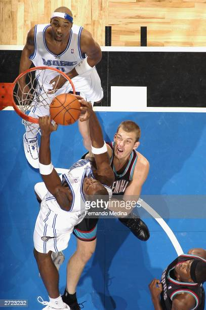 Steven Hunter of the Orlando Magic dunks over Jake Tsakalidis of the Memphis Grizzlies during a game at TD Waterhouse Centre on November 12 2003 in...