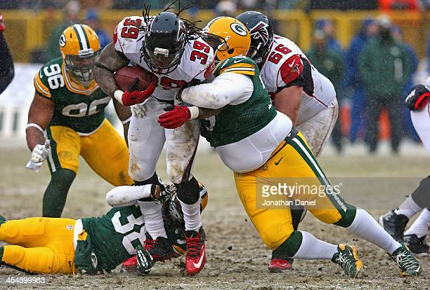 Steven Jackson of the Atlanta Falcons is tackled by Ryan Pickett and Tramon Williams of the Green Bay Packers at Lambeau Field on December 8, 2013 in...