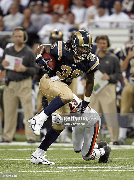 Steven Jackson of the St Louis Rams carries the ball as he is grabbed by Devin Hester of the Chicago Bears at the Edward Jones Dome on December 11...