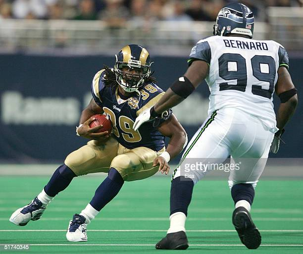 Steven Jackson of the St. Louis Rams cuts to evade Rocky Bernard of the Seattle Seahawks on November 14, 2004 at the Edward Jones Dome in St. Louis,...