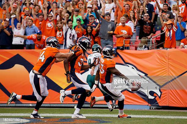 Steven Johnson of the Denver Broncos scores a touchdown after blocking a punt as teammates Jacob Tamme and David Bruton run behind during the fourth...