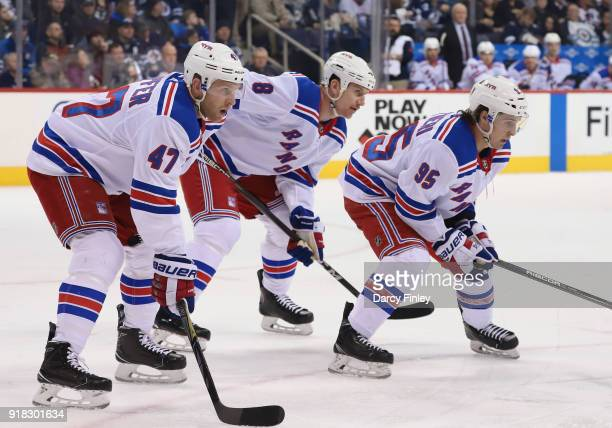 Steven Kampfer Cody McLeod and Vinni Lettieri of the New York Rangers get set for a first period faceoff against the Winnipeg Jets at the Bell MTS...