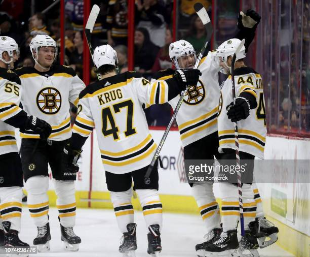 Steven Kampfer of the Boston Bruins celebrates with teammates after scoring a goal during an NHL game against the Carolina Hurricanes on December 23...