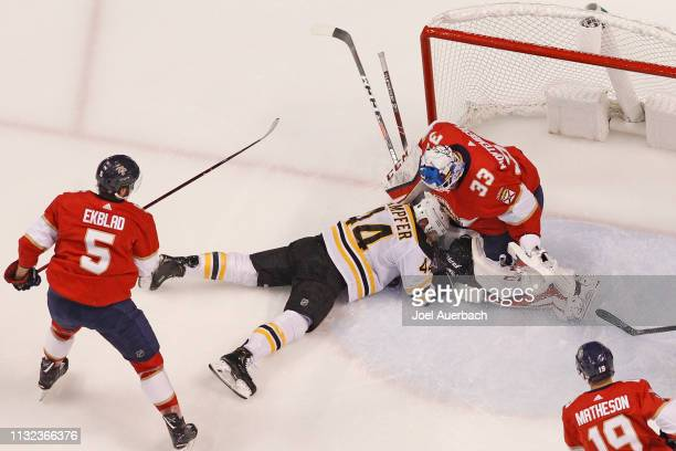Steven Kampfer of the Boston Bruins slides into Goaltender Samuel Montembeault of the Florida Panthers after being taken down during first period...