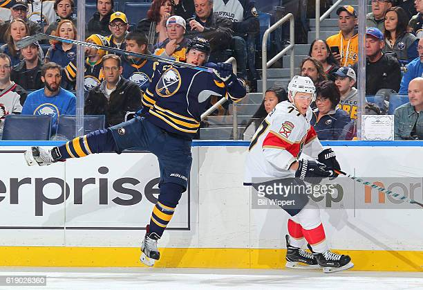 Steven Kampfer of the Florida Panthers eludes a check from Hudson Fasching of the Buffalo Sabres during an NHL game at the KeyBank Center on October...