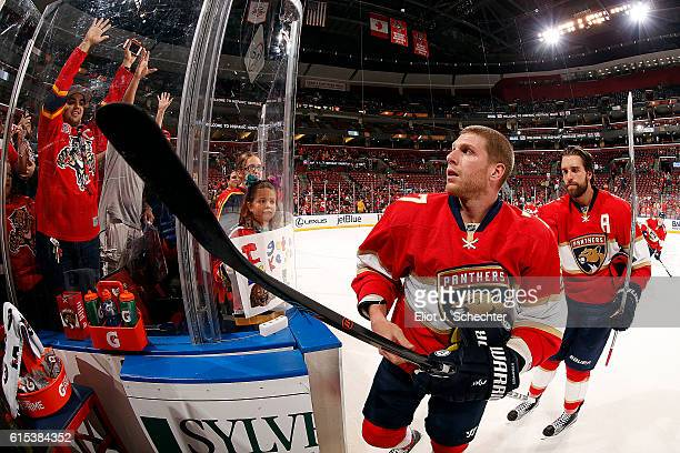 Steven Kampfer of the Florida Panthers flips a puck to fans while on his way back to the dressing room prior to the start of the game against the...