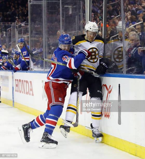Steven Kampfer of the New York Rangers hits Riley Nash of the Boston Bruins into the boards during the first period at Madison Square Garden on...
