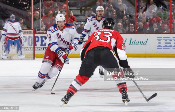 Steven Kampfer of the New York Rangers skates with the puck against Fredrik Claesson of the Ottawa Senators in the first period at Canadian Tire...