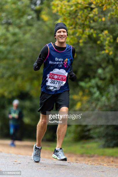 Steven Levis, a participant of Virgin Money Virtual London Marathon is seen running in cold rainy weather for Brain Research UK charity in Dulwich...