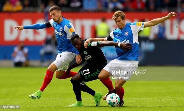 Steven Leweren and Christopher Lenz of Kiel and Khaled Narey of Greuther Fuerth battle for the ball during the Second Bundesliga match between...