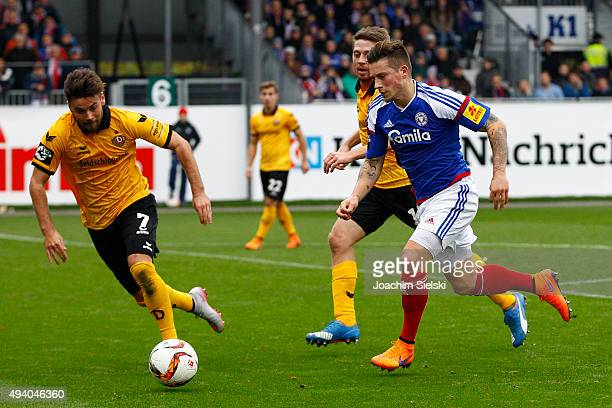 Steven Lewerenz of Kiel challenges Niklas Kreuzer and Andreas Lambertz of Dresden during the Third League match between Holstein Kiel and Dynamo...