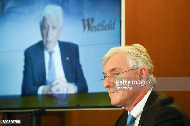 Steven Lowy cochief executive officer of Westfield Corp sits as billionaire Frank Lowy chairman is seen on a screen during a news conference in...