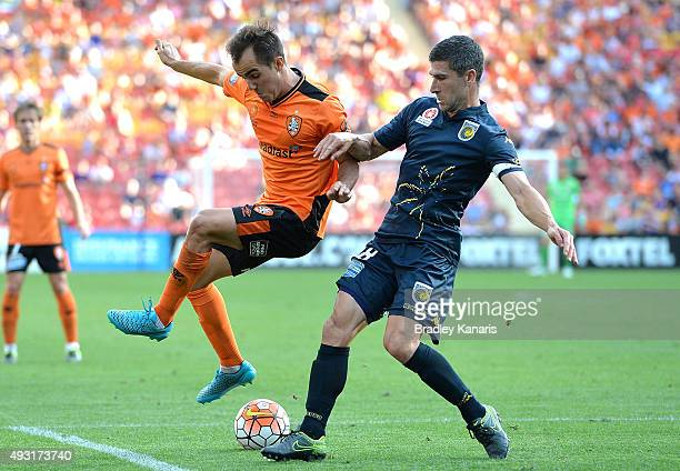 Steven Lustica of the Roar and Nick Montgomery of the Mariners challenge for the ball during the round two ALeague match between the Brisbane Roar...