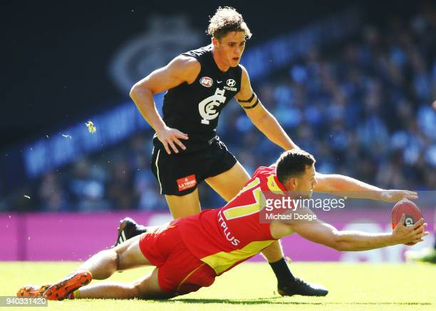 Steven May of the Suns dives for the ball against Charlie Curnow of the Blues during the round two AFL match between the Carlton Blues and the Gold...