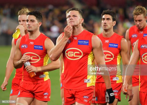 Steven May of the Suns leads his players from the field looking dejected after the round six AFL match between the Adelaide Crows and Gold Coast Suns...
