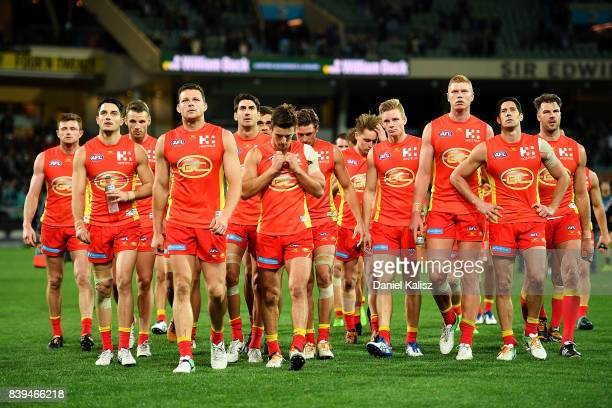 Steven May of the Suns leads his team from the field looking dejected after being defeated by the Power during the round 23 AFL match between the...