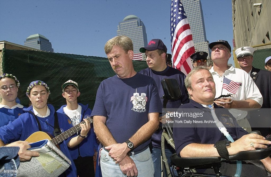 Steven McDonald, a New York City cop left quadriplegic by a gunshot wound that severed his spinal cord, sits in wheelchair as he and firefighters listen to the Dove 2000 singers at Ground Zero. McDonald led a march from St. Francis of Assisi Church on W. 32nd St., where the Rev. Mychal Judge, the Fire Department chaplain, served, to a tribute to him and others who died on Sept. 11.