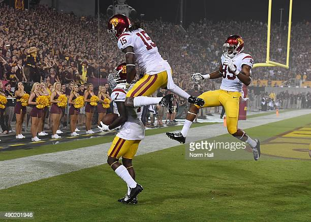 Steven Mitchell Jr of the Southern California Trojans and teammates Isaac Whitney and De'Quan Hampton celebrate a first half touchdown against the...