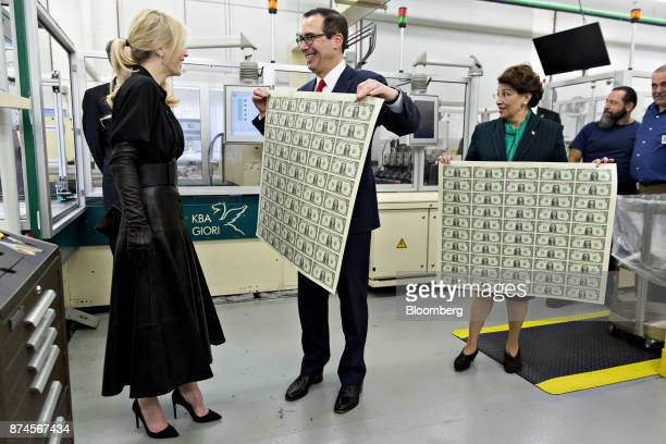 Steven Mnuchin, U.S. Treasury secretary, center, displays a 2017 50 subject uncut sheet of $1 dollar notes bearing Mnuchin's name for his wife Louise...