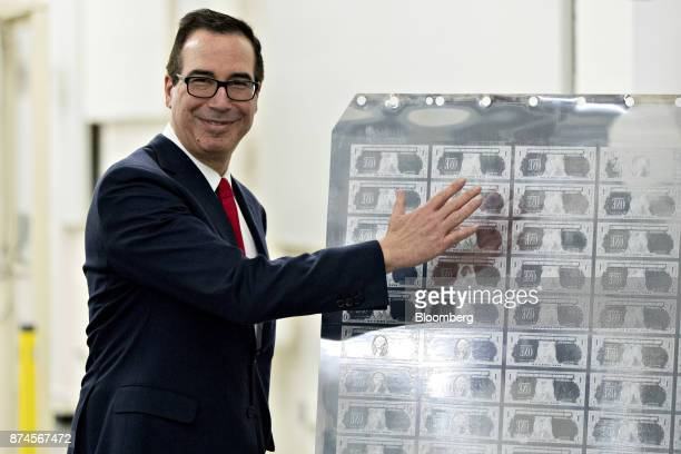 Steven Mnuchin US Treasury secretary gestures while standing next to a printing plate for $1 dollar notes bearing Mnuchin's name at the US Bureau of...