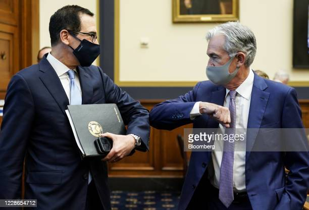 Steven Mnuchin, U.S. Treasury secretary, left, elbow bumps Jerome Powell, chairman of the U.S. Federal Reserve, before a House Financial Services...