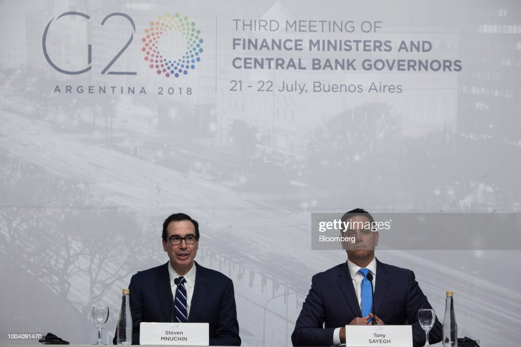 Steven Mnuchin, U.S. Treasury secretary, left, speaks as Tony Sayegh, spokesman for the U.S. Treasury Department, listens at a news conference during the G-20 finance ministers and central bankers meetings in Buenos Aires, Argentina, on Sunday, July 22, 2018. Mnuchin said that there is no chance of a currency war erupting despite U.S. President Donald Trump tweets.