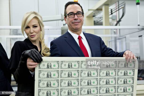 Steven Mnuchin, U.S. Treasury secretary, right, and his wife Louise Linton hold a 2017 50 subject uncut sheet of $1 dollar notes bearing Mnuchin's...