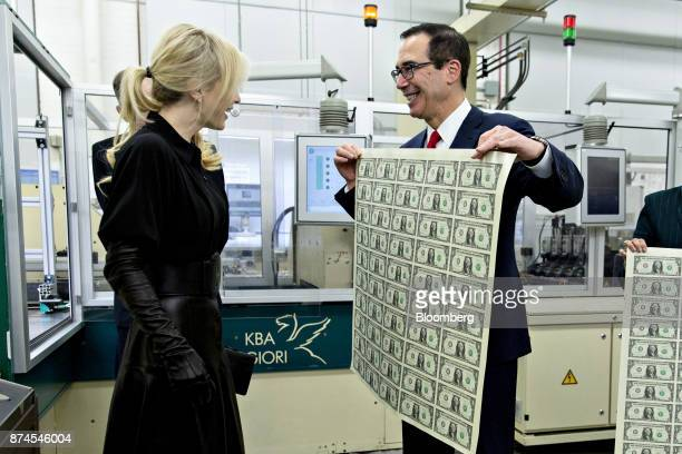Steven Mnuchin, U.S. Treasury secretary, right, displays a 2017 50 subject uncut sheet of $1 dollar notes bearing Mnuchin's name for his wife Louise...