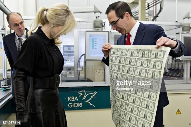 Steven Mnuchin US Treasury secretary right displays a 2017 50 subject uncut sheet of $1 dollar notes bearing Mnuchin's name for his wife Louise...