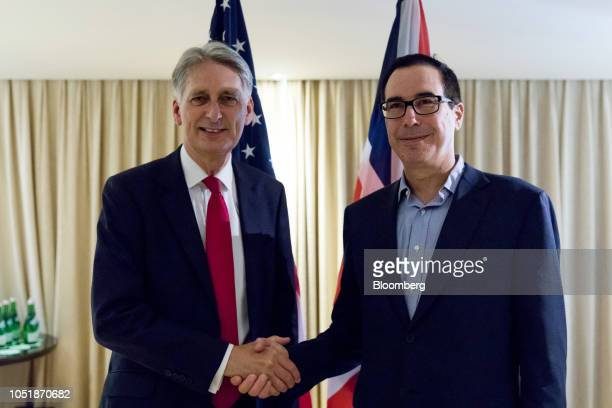 Steven Mnuchin US Treasury secretary right shakes hand with Philip Hammond UK chancellor of the exchequer at a bilateral meeting on the sidelines of...