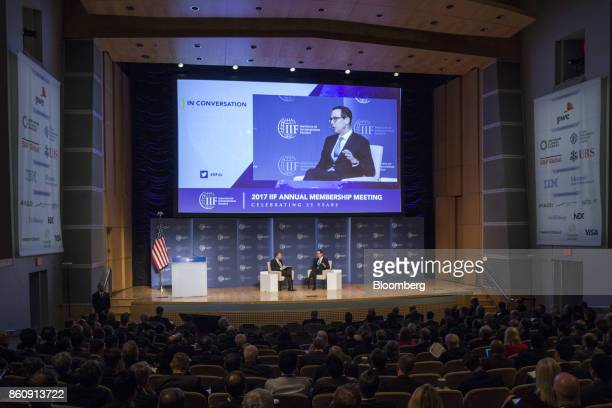 Steven Mnuchin US Treasury secretary right speaks while Tim Adams president and chief executive officer of the Institute of International Finance...