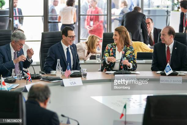 Steven Mnuchin US Treasury secretary second left reacts with Melinda Gates cochair of the Bill and Melinda Gates Foundation second right as they take...