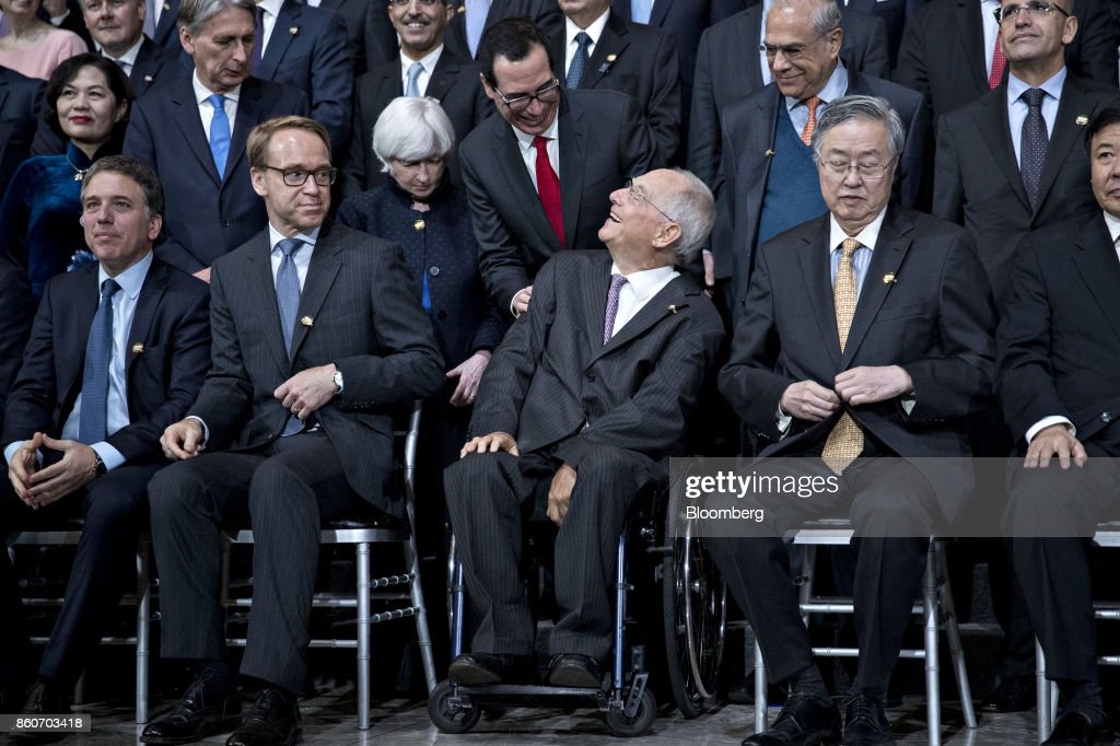Steven Mnuchin, U.S. Treasury secretary, second row center, greets Wolfgang Schaeuble, Germany's finance minister, front row center, during a Group of 20 (G-20) finance ministers and central bank governors group photo on the sidelines of the International Monetary Fund (IMF) and World Bank Group Annual Meetings in Washington, D.C., U.S., on Thursday, Oct. 12, 2017. Near-term risks to world financial stability have declined since April amid improving macroeconomic conditions and the subsiding risk of emerging-market turmoil, the IMF said in its latest Global Financial Stability Report released yesterday. Photographer: Andrew Harrer/Bloomberg via Getty Images