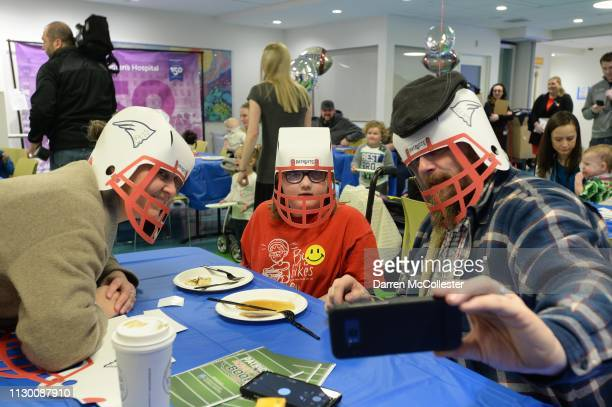 Steven Mom and Dad take a selfie with helmets during the annual New England Patriot's flipping pancakes for the kids at Boston Children's Hospital...