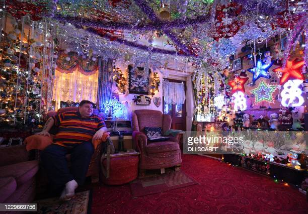 Steven Morton admires the Christmas decorations in his home as he sits in his living room in Hull, northern England on November 18, 2020. Steven and...