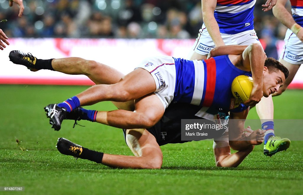 Steven Motlop of Port Adelaide gets Luke Dahlhaus of the Bulldogs caught holding the ball during the round 13 AFL match between Port Adelaide Power and the Western Bulldogs at Adelaide Oval on June 14, 2018 in Adelaide, Australia.