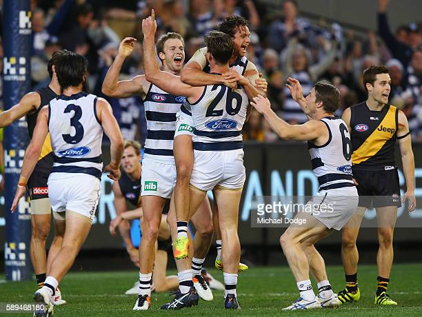 Steven Motlop of the Cats jumps on Tom Hawkins of the Cats who kicks the ball for a goal in the dying stages during the round 21 AFL match between...