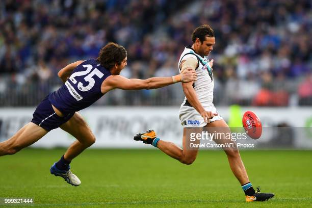 Steven Motlop of the Power is chased down by Alex Pearce of the Dockers during the 2018 AFL round 17 match between the Fremantle Dockers and the Port...