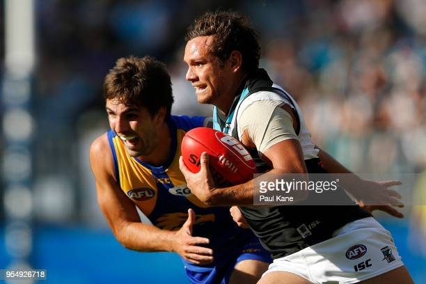 Steven Motlop of the Power runs with the ball against Andrew Gaff of the Eagles during the round seven AFL match between the West Coast Eagles and...