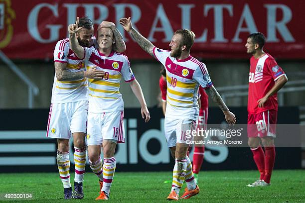 Steven Naismith celebrates scoring their sixth goal with teammates Steven Fletcher and Johnny Russell during the UEFA EURO 2016 Qualifying round...