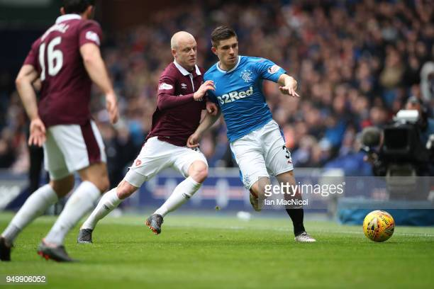 Steven Naismith of Heart of Midlothian vies with Declan John of Rangers during the Ladbrokes Scottish Premiership match between Rangers and Hearts at...