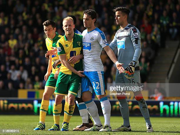 Steven Naismith of Norwich City and Daryl Janmaat of Newcastle United tussle during the Barclays Premier League match between Norwich City and...