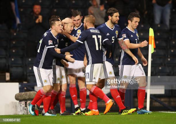 Steven Naismith of Scotland celebrates with team mates as Berat Gjimshiti of Albania scores an own goal for their first goal during the UEFA Nations...
