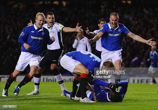 Steven Naismith Steven Whittaker and Kenny Miller of Rangers rush to congratulate the prone Edu of Rangers after he scored during the UEFA Champions...