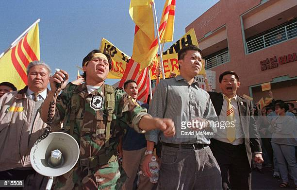 Steven Nguyen and other American Vietnamese marchers demostrate against shop owner Truong Van Tran February 15 who placed a Communist flag and a...